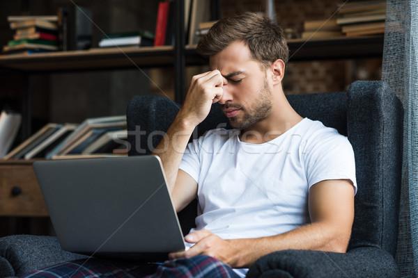 Fatigué homme utilisant un ordinateur portable jeune homme maison vêtements Photo stock © LightFieldStudios