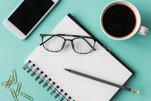 top view of notebook with cup of coffee and smartphone with glasses mock-up, small office home offic Stock photo © LightFieldStudios