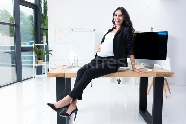 pregnant businesswoman sitting on worktable Stock photo © LightFieldStudios
