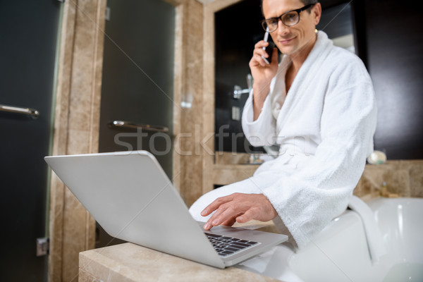 Empresário roupão de banho usando laptop hotel banheiro Foto stock © LightFieldStudios