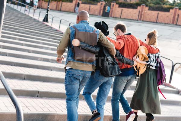 Multiculturele vrienden lopen straat achteraanzicht samen Stockfoto © LightFieldStudios