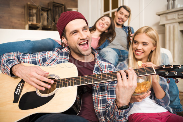 Group of happy young friends enjoying guitar at home Stock photo © LightFieldStudios