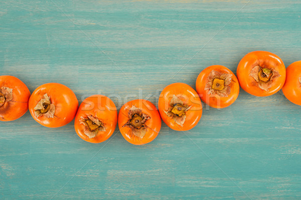 top view of row of persimmons on turquoise wooden table Stock photo © LightFieldStudios