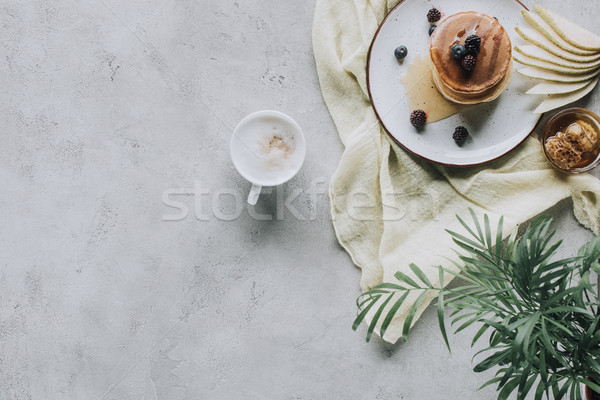 top view of sweet tasty pancakes with berries and cappuccino on grey  Stock photo © LightFieldStudios