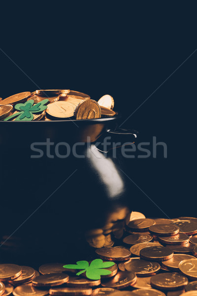 black pot with golden coins on surface isolated on black, st patricks day concept Stock photo © LightFieldStudios