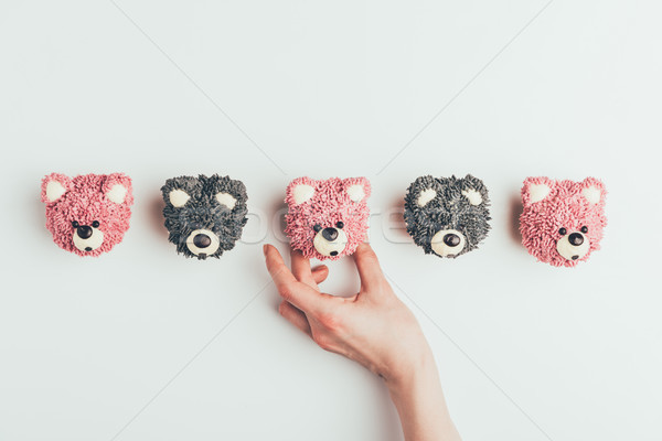 cropped shot of human hand and delicious muffins in shape of bears isolated on grey   Stock photo © LightFieldStudios