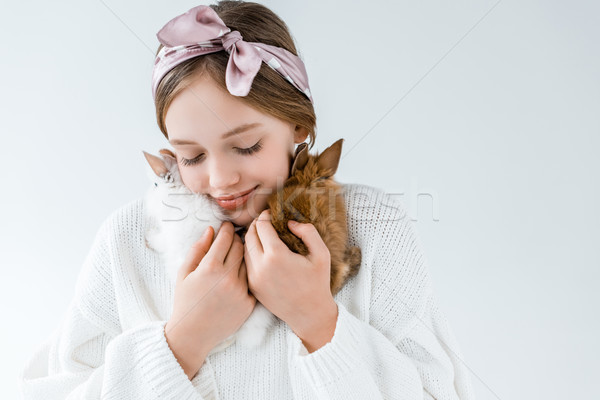 happy little girl holding cute furry rabbits isolated on white Stock photo © LightFieldStudios