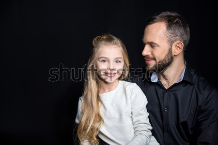 portrait of smiling woman looking to camera while bonding to man on black Stock photo © LightFieldStudios