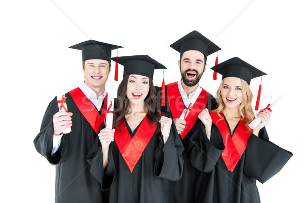 Happy young students in academic caps holding diplomas and smiling at camera  Stock photo © LightFieldStudios