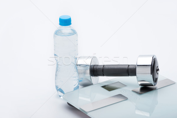 metallic dumbbell, scales, towel and bottle with water isolated on white. equipment sport and health Stock photo © LightFieldStudios