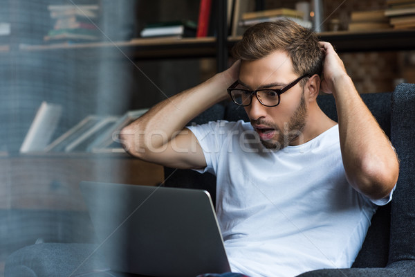 Shocked man using laptop Stock photo © LightFieldStudios