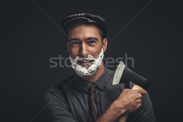 Homme ax souriant jeune homme cap crème Photo stock © LightFieldStudios