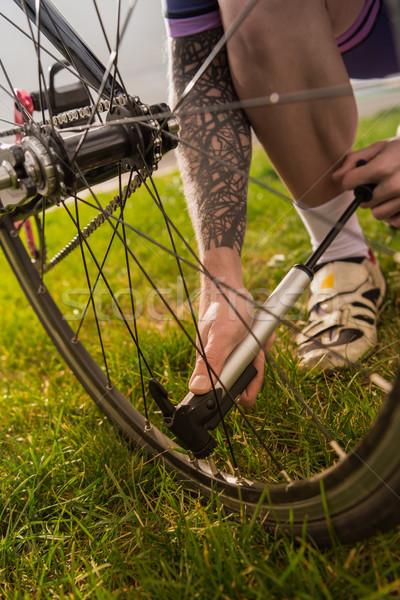 Stock photo: man pumping bicycle wheel