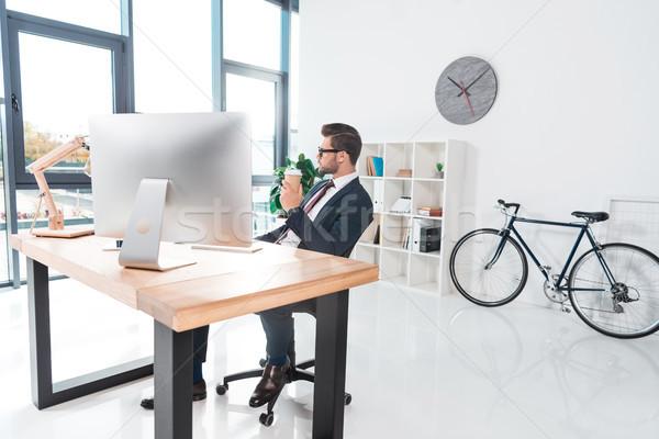 üzletember dolgozik asztali számítógép iszik kávé papír Stock fotó © LightFieldStudios