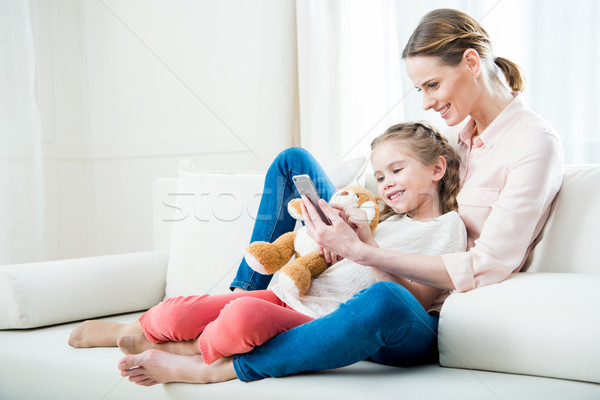 Stock photo: side view of cheerful mother and daughter using smartphone together