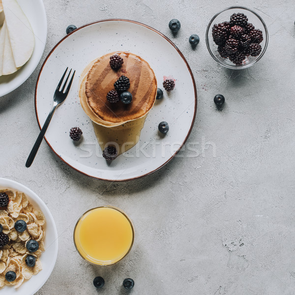 top view of delicious homemade pancakes, glass of juice and muesli on grey  Stock photo © LightFieldStudios