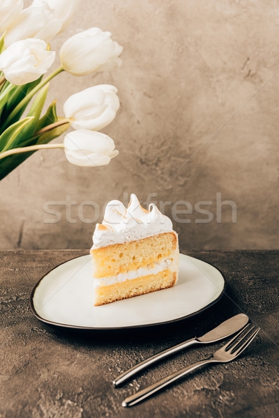 close-up view of delicious piece of cake with whipped cream and beautiful white tulips Stock photo © LightFieldStudios