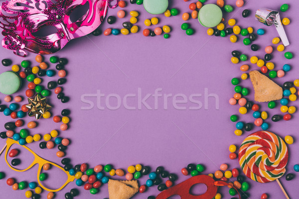 top view of arranged masquerade masks, candies and cookies isolated on purple Stock photo © LightFieldStudios