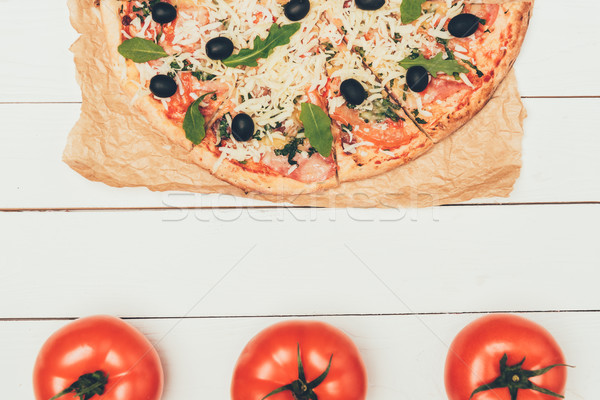 Delicious Italian pizza and red tomatoes on white wooden background Stock photo © LightFieldStudios