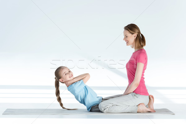 Side view of happy mother training daughter on yoga mat   Stock photo © LightFieldStudios