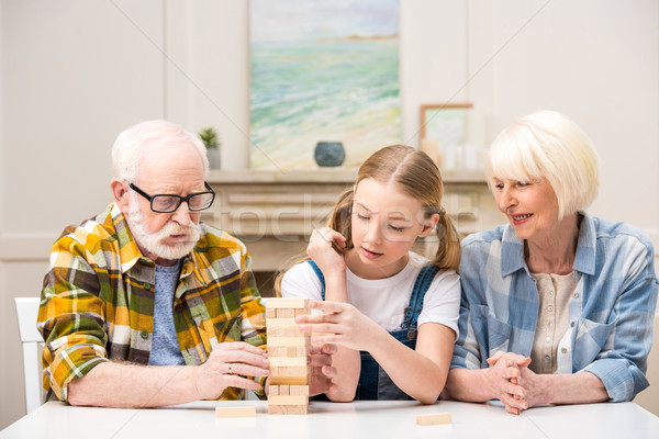 Concentrated little girl with grandparents playing jenga game together at home   Stock photo © LightFieldStudios