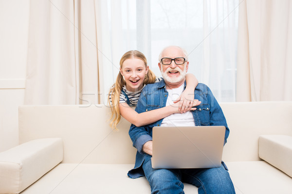 Happy little girl hugging smiling grandfather sitting on sofa with laptop Stock photo © LightFieldStudios
