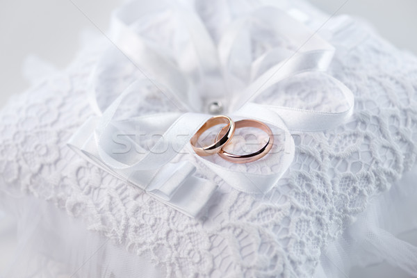 Close-up view of golden wedding rings on decorative white lace pillow Stock photo © LightFieldStudios