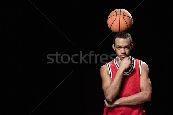 Young smiling basketball player standing with ball on head on black  Stock photo © LightFieldStudios