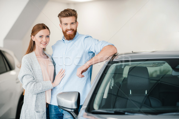 Happy couple embracing and standing at car in dealership salon  Stock photo © LightFieldStudios