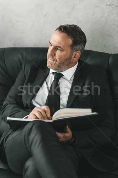 thoughtful businessman with notebook Stock photo © LightFieldStudios
