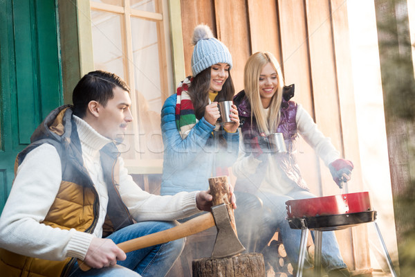 Young man chopping firewood with axe while happy women drinking tea near grill Stock photo © LightFieldStudios