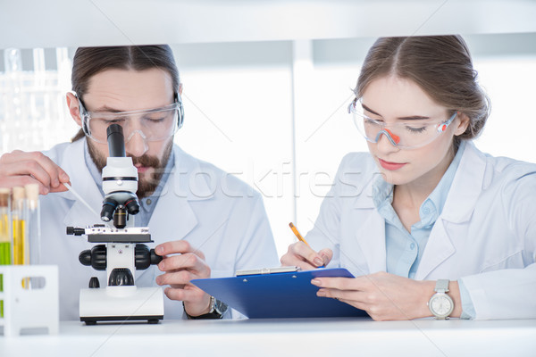 Chemists working with microscope Stock photo © LightFieldStudios