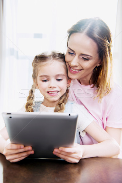 Stock photo: Happy mother and daughter using digital tablet at home