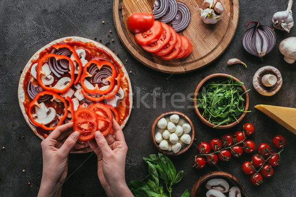 cropped shot of woman spreading bell pepper slices onto pizza on concrete table Stock photo © LightFieldStudios