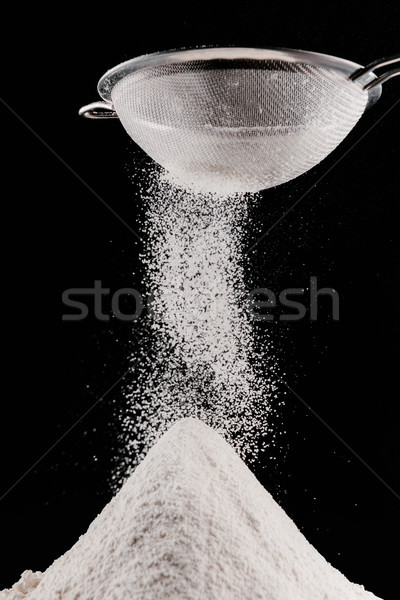 flour falling from sieve on pile isolated on black Stock photo © LightFieldStudios