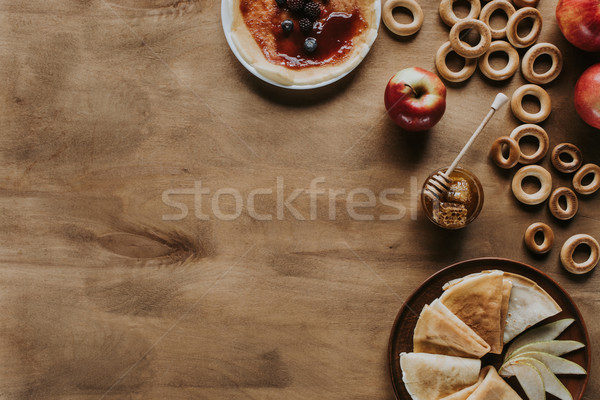 top view of tasty pancakes with apples, berries, honey and bagels on wooden table Stock photo © LightFieldStudios
