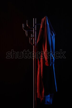 cloth hanging on coat rack under toned light isolated on black Stock photo © LightFieldStudios
