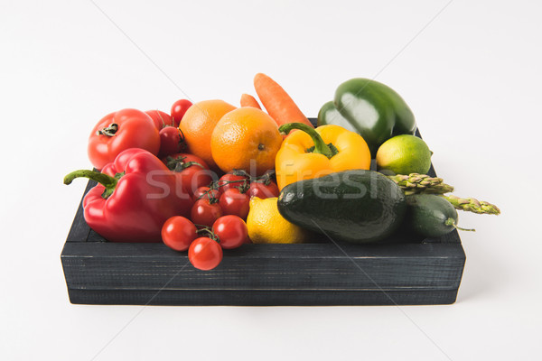 Eating healthy concept with vegetables and fruits in dark wooden box isolated on white background Stock photo © LightFieldStudios