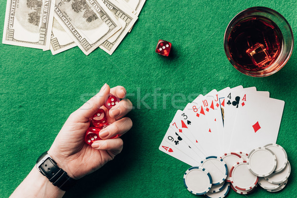 Woman holding dice by casino table with money and chips Stock photo © LightFieldStudios