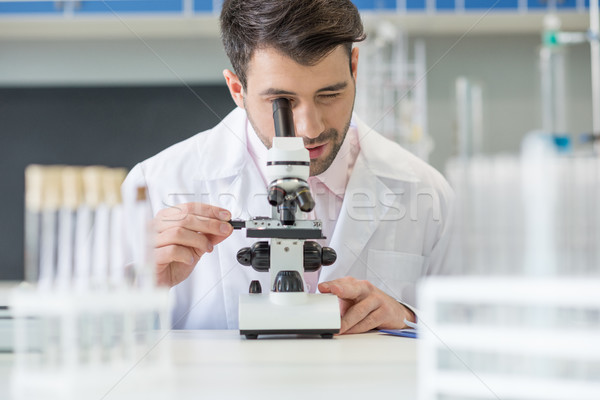 Stock photo: Man scientist in white coat working with microscope in lab