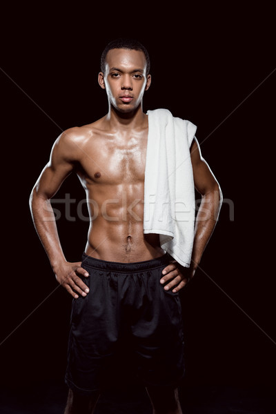 portrait of confident african sporty man with towel on shoulder on black Stock photo © LightFieldStudios