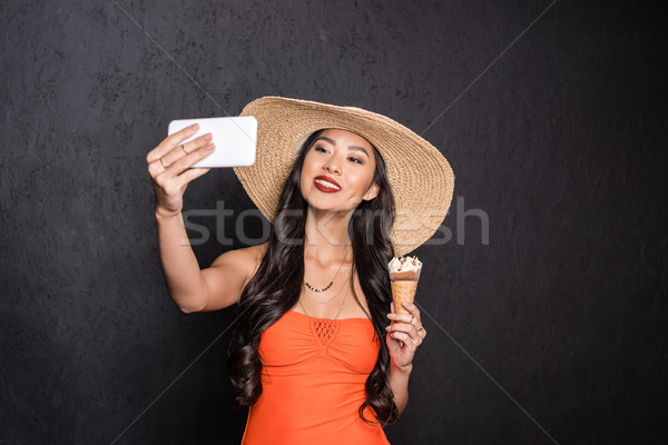 Stock photo: Woman holding ice-cream and taking selfie