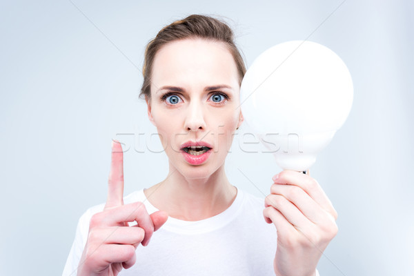 woman with light bulb pointing up Stock photo © LightFieldStudios