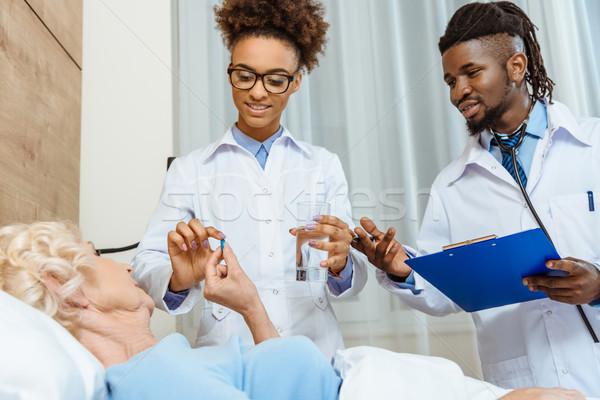 Doctors handing sick woman medicine Stock photo © LightFieldStudios