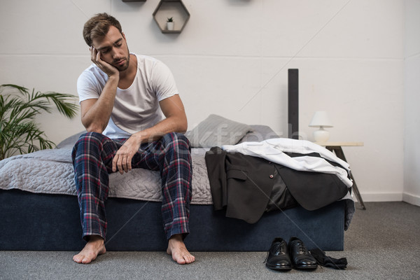 Somnolent homme séance lit jeunes maison Photo stock © LightFieldStudios