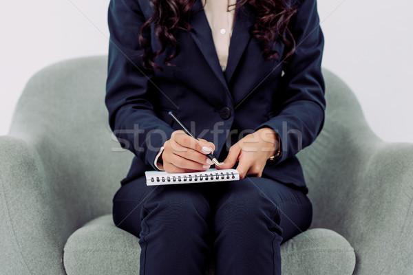 Piśmie notatnika shot kobieta interesu posiedzenia fotel Zdjęcia stock © LightFieldStudios