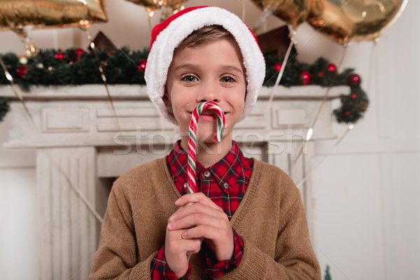 boy in santa hat with candy cane Stock photo © LightFieldStudios