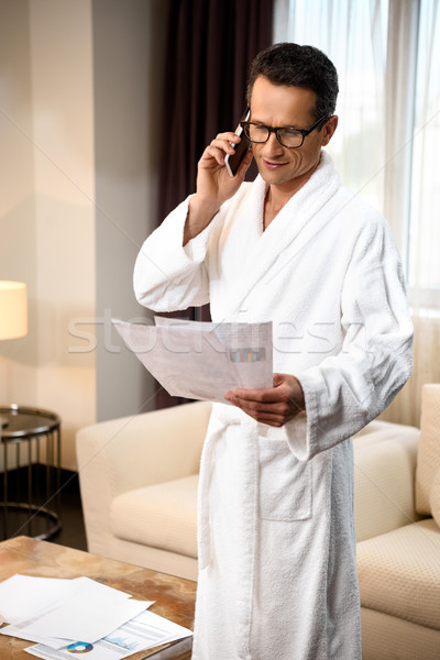 Businessman reading paperwork and talking on phone Stock photo © LightFieldStudios