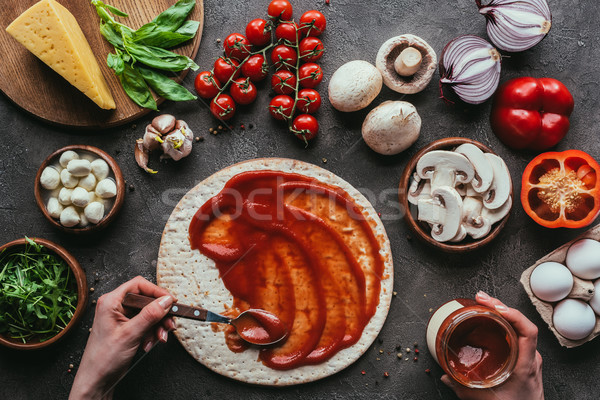 cropped shot of woman spreading ketchup onto pizza dough on concrete table Stock photo © LightFieldStudios