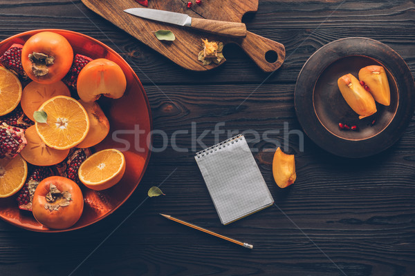 top view of persimmons, oranges and pomegranates with notebook on table Stock photo © LightFieldStudios